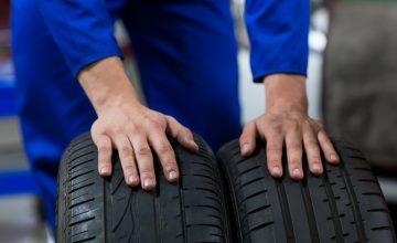 Hands of mechanic touching tyres in repair garage